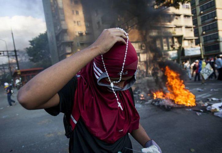 Un manifestante se coloca un rosario durante la protestas contra el presidente Nicolás Maduro, en Caracas, Venezuela. (Agencias)