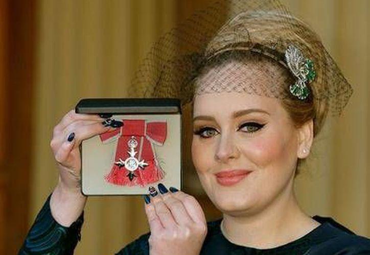 La cantante Adele Adkins posa con el distintivo que le otorgór el príncipe Carlos como Miembro de la Orden del Imperio Británico por sus servicios a la música, este jueves, en el Palacio de Buckingham en Londres. (AP Foto/John Stillwell)