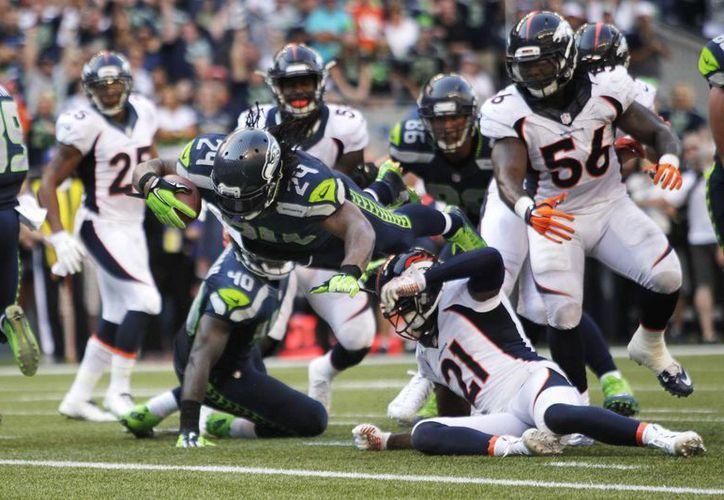 Marshawn Lynch, corredor de los Seahawks de Seattle, se lanza para hacer la anotación que definió el partido frente a los Broncos de Denver (AP Foto/John Froschauer)