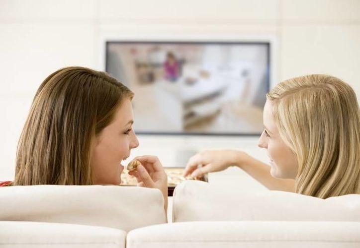 Cuando las personas estaban distraídas, mirando televisión o en otras cosas, tendían a comer mayor cantidad de una vez. (Contexto/Internet)