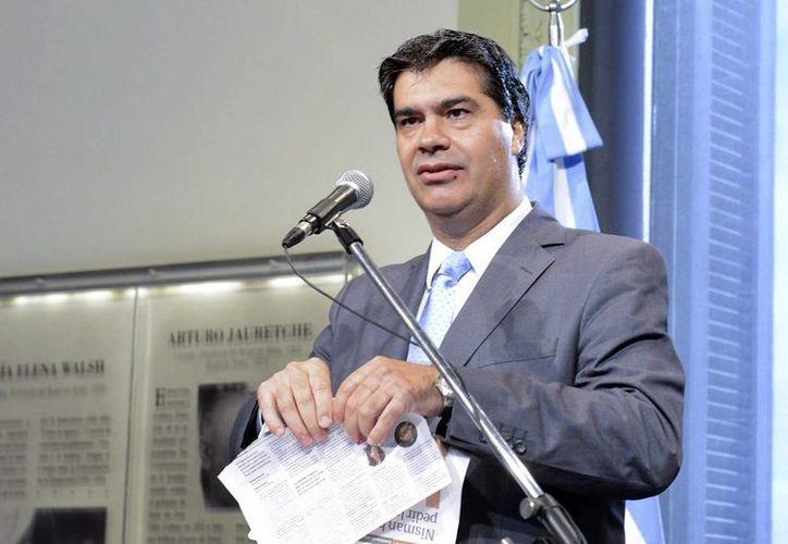 Imagen cedida por Telam del jefe del Gabinete argentino, Jorge Capitanich, mientras hace trizas dos páginas del diario Clarín, este 2 de febrero, en una rueda de prensa. (EFE/Telam)