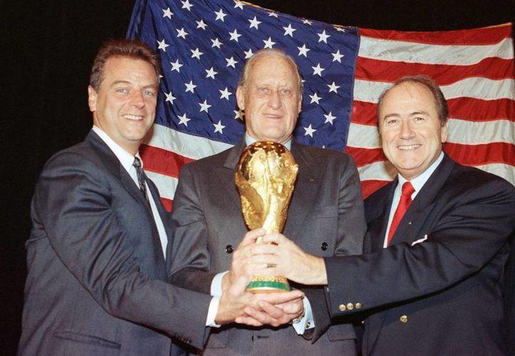 Joao Havelange (centro) sostiene la Copa del Mundo 1994, junto con Alan I Rothenberg (izq.) y  Joseph S. Blatter, en Nueva York. El expresidente de la FIFA murió este martes. (Archivo/AP)