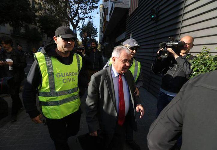 El tesorero de Convergencia, Andreu Viloca, a su entrada en la sede del partido, escotado por agentes de la Guardia Civil. (Danny Caminal/elperiodico.com)