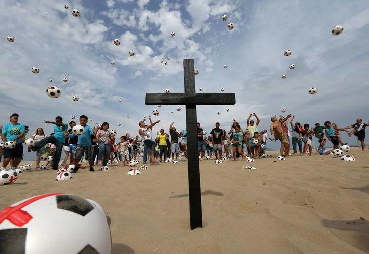 Los balones fueron  pateados simultáneamente al aire y recogidos por niños pobres, a quienes fueron donados. (EFE)