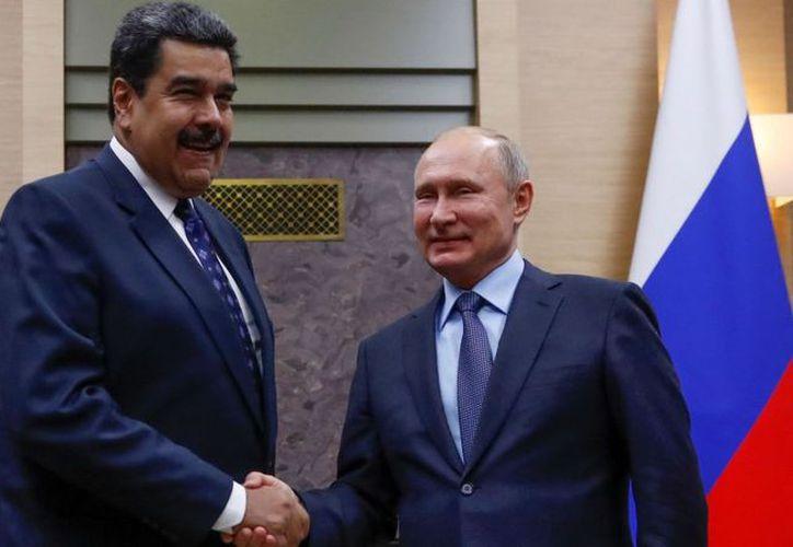 El presidente ruso Vladimir Putin, le da la mano a su homólogo venezolano Nicolás Maduro, durante una reunión en las afueras de Moscú. (Maxim Shemetov / Reuter)