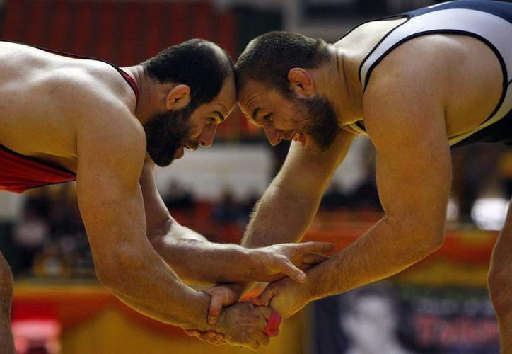 El luchador iraní Fardin Masoumi (izq), compite con el estadounidense Tervel Dlagnev en un torneo de lucha libre en Teherán, Irán. (AP/Vahid Salemi)
