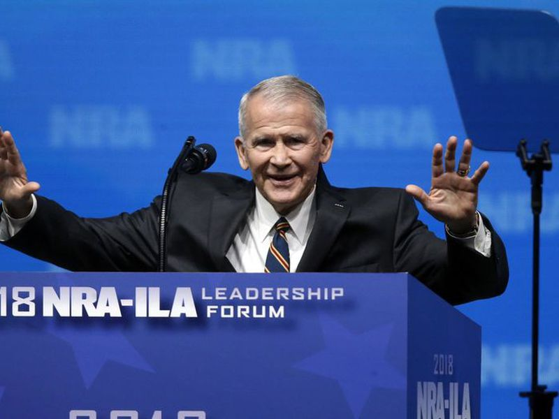 Former U.S. Marine Lt. Col. Oliver North acknowledges attendees as he gives the Invocation at the National Rifle Association-Institute for Legislative Action Leadership Forum in Dallas.