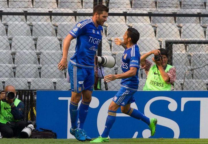 El francés Andre-Pierre Gignac (i) celebra con su compañero Javier Aquino la anotación al minuto 26}8 que le dio el triunfo a los Tigres de la UANL, 0-1 en el Estadio Azteca. (Notimex)