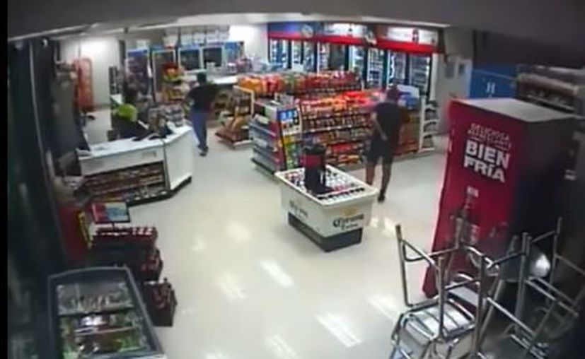 Después del forcejeo el ladrón suelta lo robado, cae sangre al piso y el empleado de 22 años se dirige a un segundo ladrón que trata de evadirlo. (Captura)