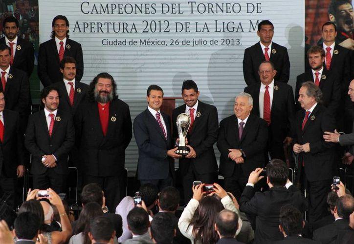 Peña Nieto y el capitán de los Xolos, Javier Gandolfi, sostienen el trofeo de campeón de la Liga Mx. (Notimex)