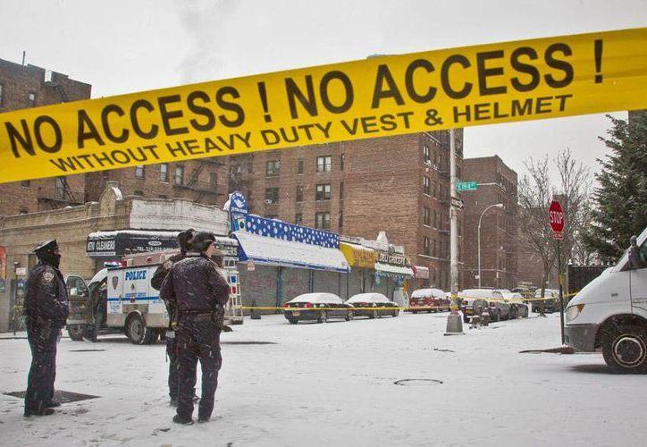Policías de Nueva York resguarda en el área en donde 2 de sus compañeros fueron baleados, durante un asalto. (AP)