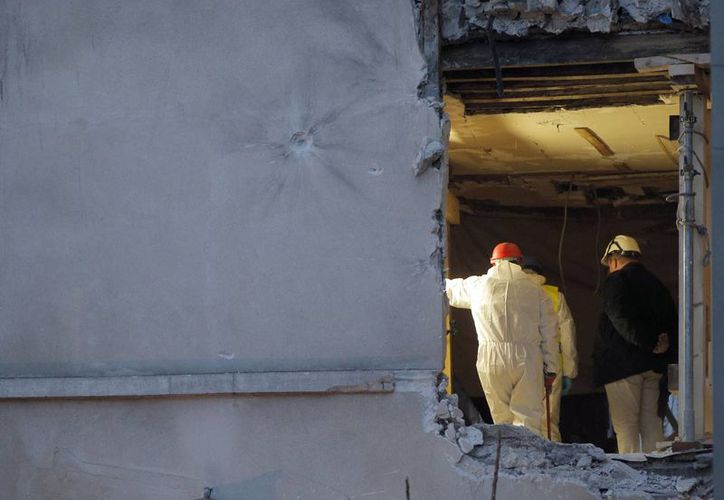 Autoridades trabajan en el interior del edificio de Saint-Denis, donde se realizó un operativo para encontrar al autor de los atentados en París. En el lugar encontraron el cuerpo de una mujer, de la cual no se sabe su identidad. (Agencias)