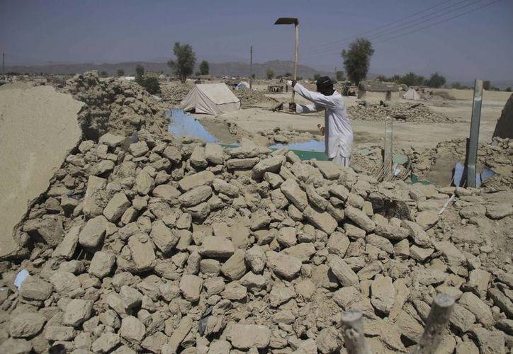 Tras el sismo en Awaran un hombre trata de retirar los escombros en la zona que era su hogar en Pakistán. (EFE)