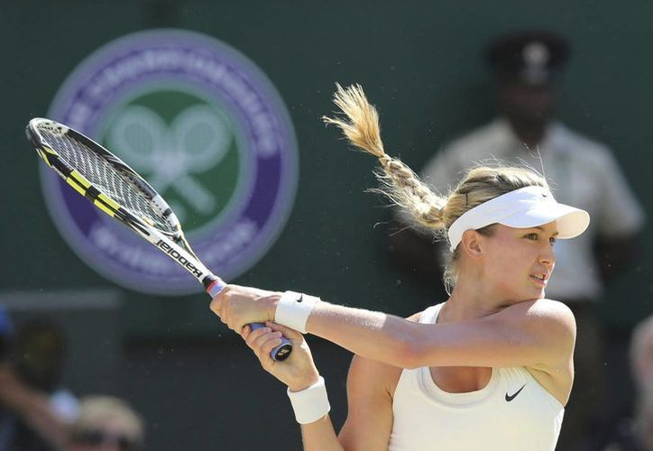 La tenista canadiense Eugenie Bouchard devuelve una bola a la rumana Simona Halep durante su encuentro en la semifinal femenina del torneo de Wimbledon celebrada en el club de tenis All England Lawn de Londres. (EFE)