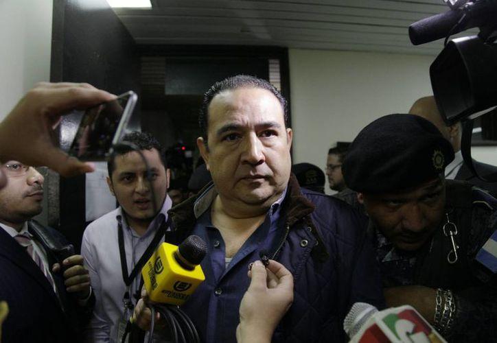 Samuel Everardo Morales, hermano del presidente de Guatemala, Jimmy Morales, es escoltado por policías al arribar a la corte de Guatemala, el 18 de enero de 2016. Está acusado de corrupción. (AP Photo/Luis Soto)
