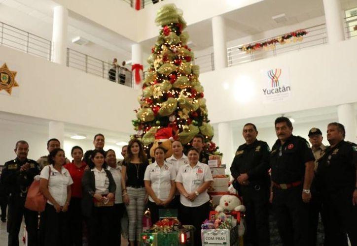 La presidenta del Patronato Pro-Hijo del Policía, María Angélica Fernández de Saidén (al centro, de pantalón claro), realizó el encendido del Árbol de Navidad de la SSP. (Foto cortesía)