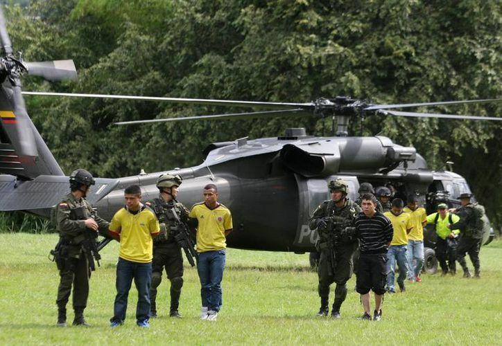 Miembros de la Policía custodian a 17 presuntos guerrilleros de las FARC en Cali, Colombia. (EFE)