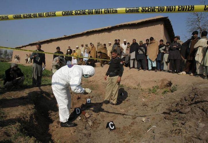 Peritos colectan evidencia a las afueras de la residencia de un líder antitalibán que fue acribillado, junto con ocho integrantes de su familia, por un grupo de desconocidos. (Agencias)