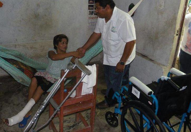 El presidente de Apoyo Ciudadano, Luis Cauich Matos, entrega apoyo a un mujer necesitada de Kanasín. (SIPSE)