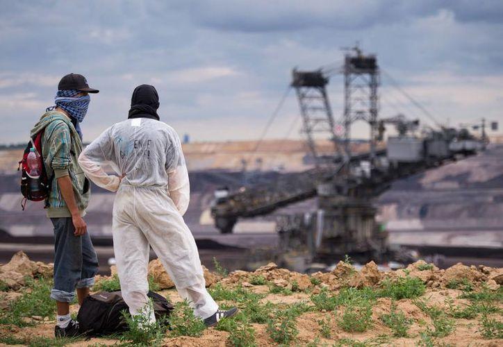 Manifestantes observan una excavadora en una mina de carbón a cielo abierto en Garzweiler, Alemania. (Agencias)