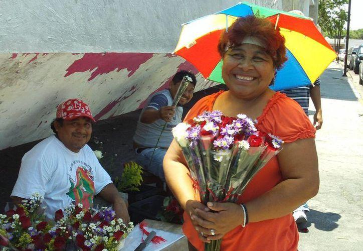 El ingenio ante todo para ofertar sus flores por el Día de las Madres, y protegerse del sol. (SIPSE)