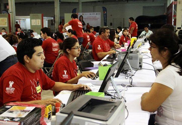 Imagen de empleados del Ibecey que capturan los datos para la adquisición de becas a estudiantes yucatecos, en el Centro de Convenciones Siglo XXI. (Milenio Novedades)