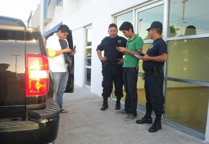 Policías flanquean al individuo acusado de cobrar por anticipado cuatro boletos de una excursión inexistente. (Redacción/SIPSE)