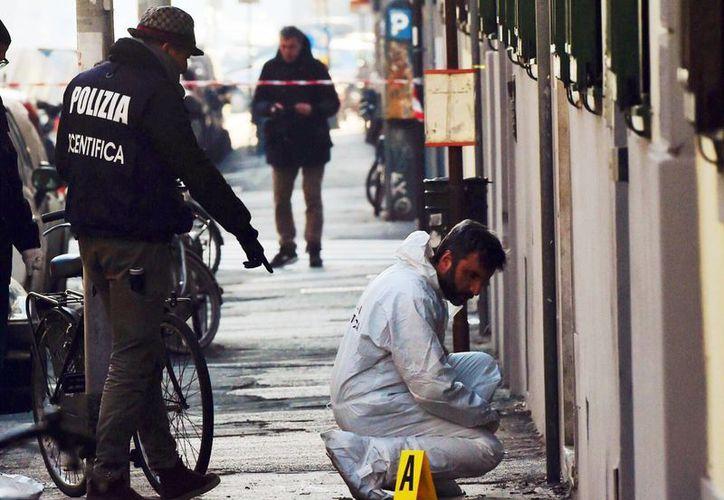 Policías forenses colectan evidencia en el sitio de la explosión de una bomba frente a una librería en Florencia, Italia, este domingo. Un agente resultó herido en la explosion. (Maurizio Degl'Innocenti/ANSA via AP)