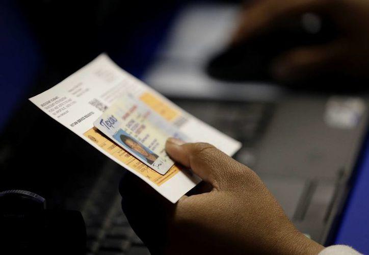 Un funcionario electoral verifica una identificación con fotografía del elector en un sitio de votación anticipada en Austin, Texas. (Agencias)