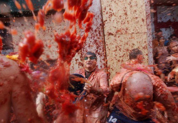 Vista general de la Tomatina en la calle principal de la localidad valenciana de Buñol que celebra el 70 aniversario de su tradicional fiesta, en la que participan más de 22 mil personas de 96 nacionalidades diferentes. (EFE)