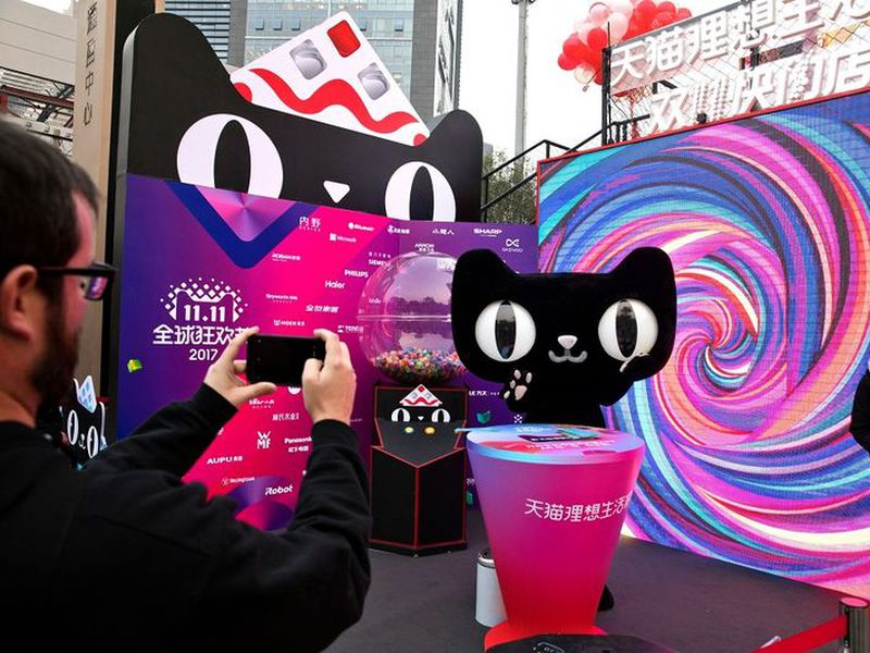 A mascot for Tmall, an online shopping website owned by Alibaba, promotes Singles Day in Beijing, China. Executives from five major brands told AP that after they refused exclusive deals with Alibaba and instead participated in big promotions with its archrival JD.com, traffic to their products on Alibaba's Tmall fell, hurting sales. Alibaba says it has never punished anyone.
