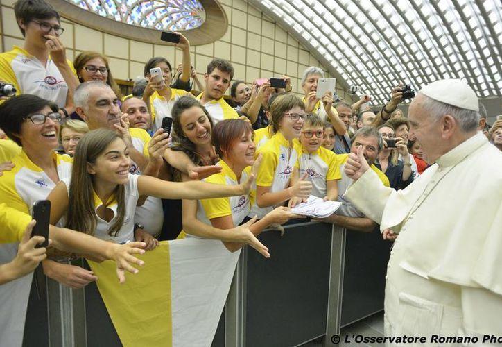 El Papa Francisco saluda a un grupo de jóvenes a su llegada al Aula Paulo VI del Vaticano para su audiencia general del miércoles 12 de agosto de 2015, donde disertó sobre la fiesta, el trabajo y la oración. (AP)