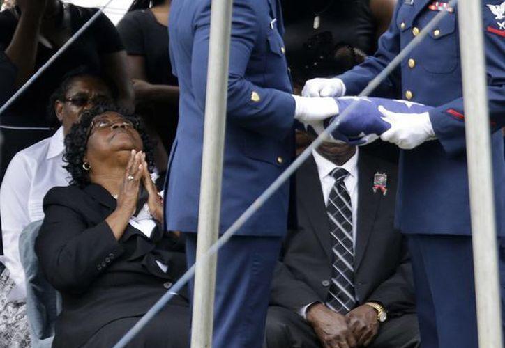 Guardias de honor pliegan una bandera estadounidense que cubría el féretro de su Walter Scott para entregarla a Judy Scott (izq), madre del afroamericano. (Agencias)