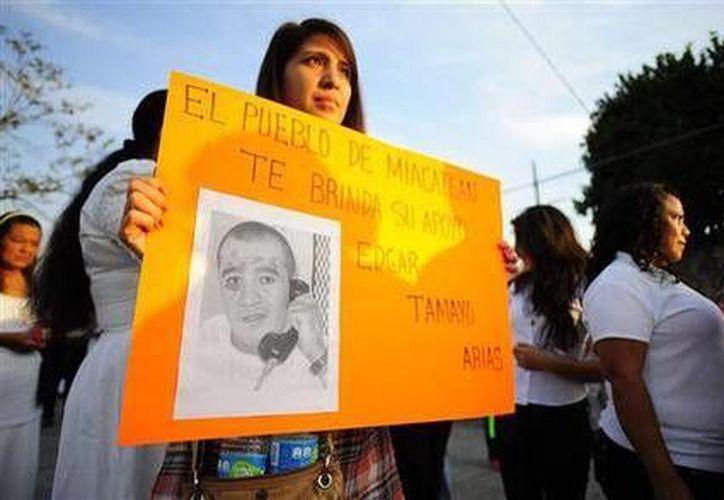Imagen del 19 de enero de 2014, una mujer sostiene un cartel con una foto de Edgar Tamayo, durante una protesta para exigtir el perdón, en su pueblo natal de Miacatlán, México. (Foto AP/Tony Rivera)