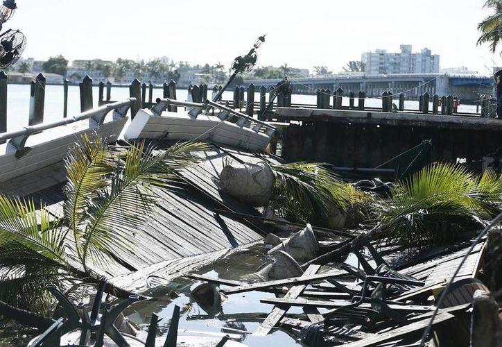 Buzos se dedicaron a revisar las aguas luego del derrumbe de la terraza del Shuckers Bar &amp Grill en Miami.  (Agencias)