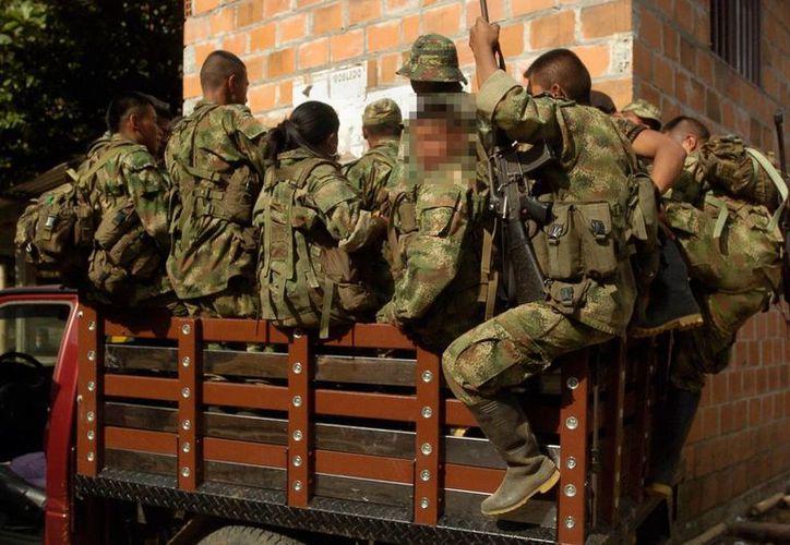 Un grupo de milicianos de las FARC se moviliza en una zona rural del municipio de Caloto al norte del Cauca, Colombia. (EFE)