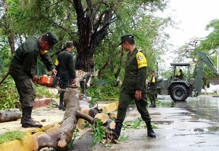 En la imagen, personal del Ejército realiza tareas de ayuda después de un ciclón, como parte del protocolo de ayuda ante un evento de esta magnitud. (Milenio Novedades)