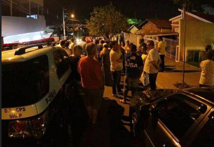 Vecinos se reúnen alrededor de la casa donde un hombre asesinó a más de una decena de personas, en una ciudad de San Pablo, BRasil. (clarin.com)