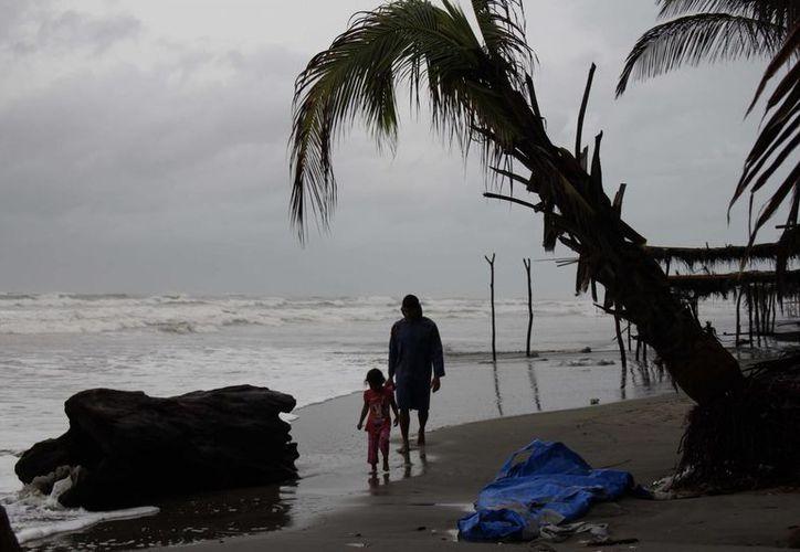 Un hombre y su pequeña caminan entre las afectaciones propiciadas por un huracán en el Pacífico mexicano. (Archivo/EFE)