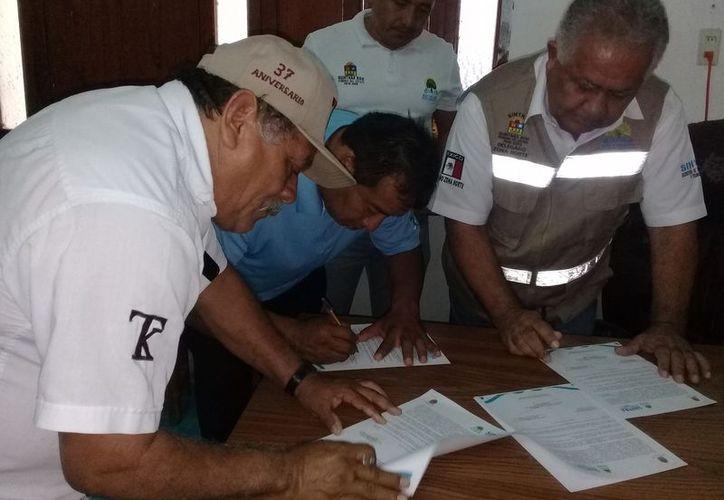 Líderes taxistas y las autoridades durante la firma de un acuerdo. (Raúl Balam/SIPSE)