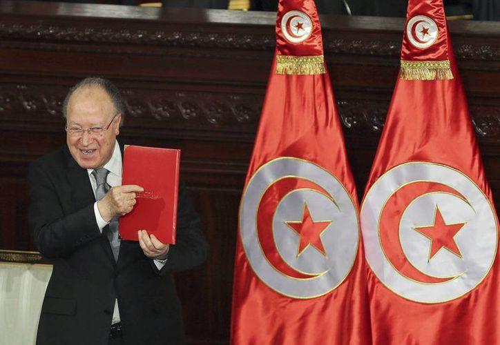 El portavoz de la Asamblea Constituyente Mustafá Ben Jaafar muestra un ejemplar de la nueva constitución tunecina. (EFE)