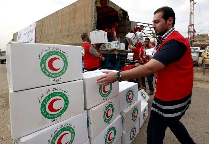 Miembros de la Sociedad de la Media Luna Roja Iraquí llenan un camión con suministros de ayuda humanitaria para Siria. (Agencias)