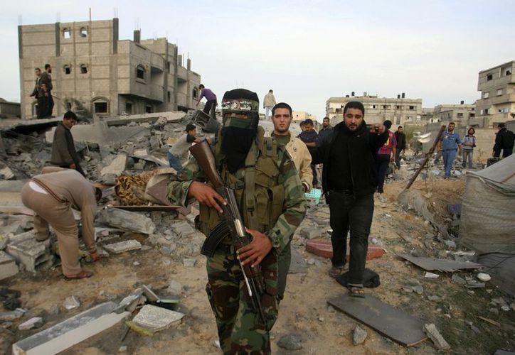 Un miliciano del grupo extremista palestino Hamas camina entre los escombros de la casa del militante Mohammad Abu Shmala después de un bombardeo israelí en Rafa. (Agencias)