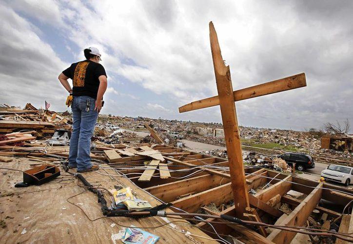 Una de las víctimas observa la casa de sus padres totalmente destruida por el tornado en Westmoor en el sur de Oklahoma City. (Agencias)