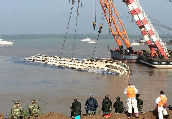 Dos grúas intentan enderezar el casto de un crucero que naufragó en el río Yangtsé en la provincia china de Hubei, el 5 de junio de 2015. (Agencias)