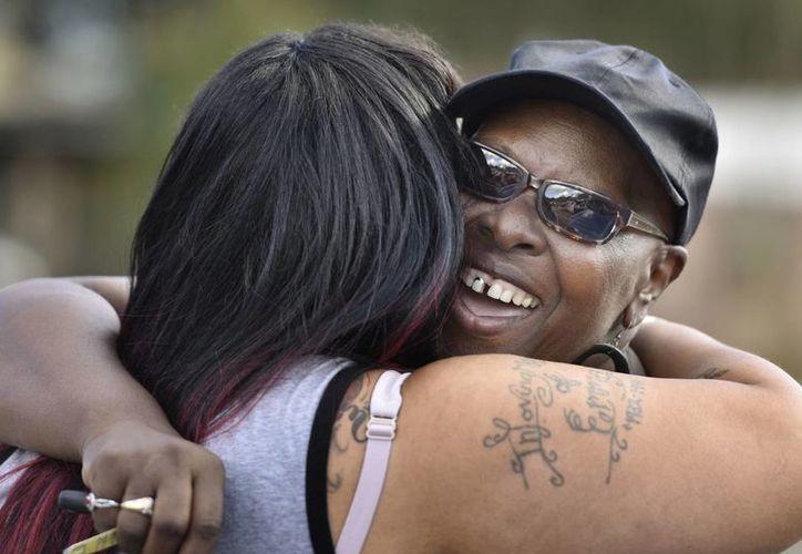 Velma Aiken, la abuela paterna de Kamiyah Mobley, quien fue secuestrada como hace 18 años, recibe un abrazo de felicitación de un miembro de la familia después de que Mobley fue encontrada este viernes 13 de enero de 2017 en Jacksonville, Florida (Will Dickey / El Florida Times-Unión vía AP)