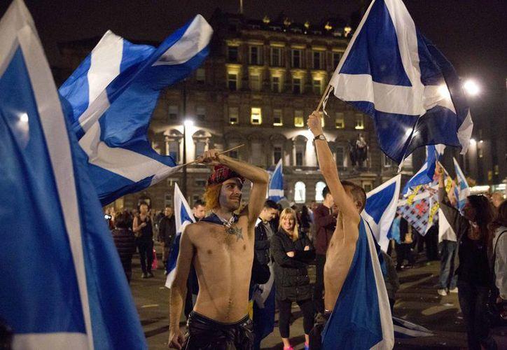 Miles de escoceses permanecen toda la noche despiertos para conocer los primeros resultados del referéndum que les daría, o no, su independencia del Reino Unido. (AP)