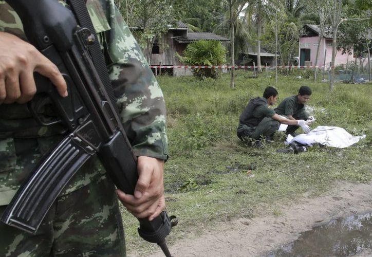 Militares realizan el levantamiento de los cadáveres de los insurgentes masacrados. (EFE)