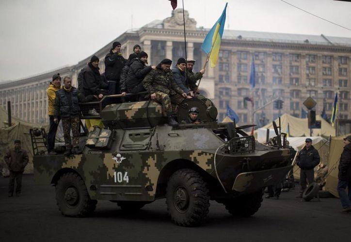 Detractores de Yanukovych protestan a bordo de un vehículo militar en la Plaza de la Independencia en Kiev. (Agencias)