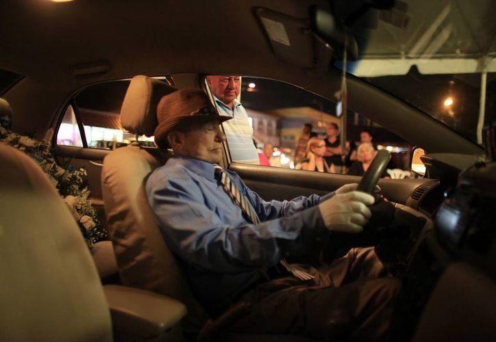 El cadáver del taxista Víctor Pérez Cardona es velado al volante del automóvil que condujo los últimos años de su vida en Aguas Buenas, Puerto Rico. (Agencias)